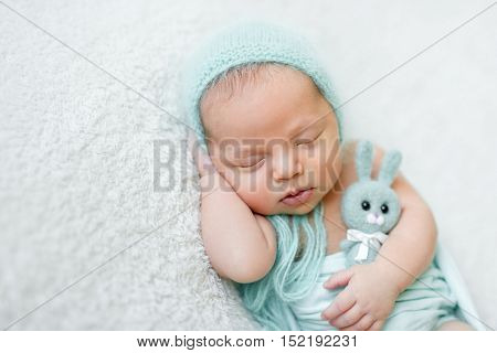 lovely sleeping baby with blue hat, panties and toy on white blanket close up