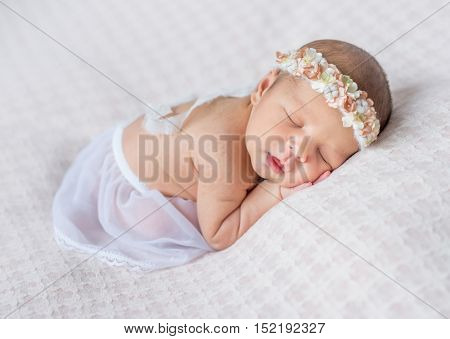 lovely newborn girl with headband sleeping on her stomach and hands under her head, covered with white shawl