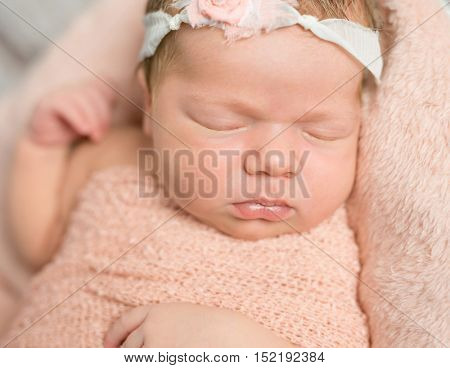 cute face of sleepy newborn baby with hair band lying on soft blanket
