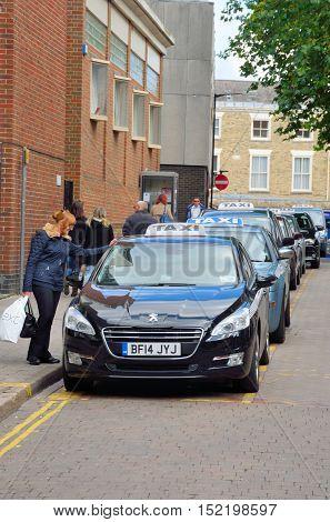 Canterbury United Kingdom - September 30 2016: Woman at English Taxi Rank talking to driver