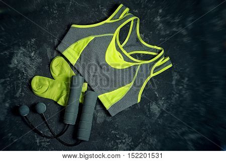Sports apparel unusual skipping rope with balls instead of ropes and socks on a dark cement background .Sport and healthy lifestyle concept. Clothing equipment and fitness accessories.