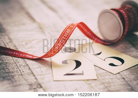 Old christmas concept - red ribbon with advent calendar an old wooden background closeup