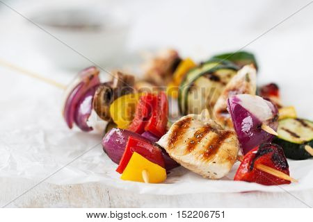Closeup of chicken skewers or shashlik with grilled vegetables