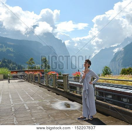 Portrait of young brunette woman in long grey dress standing outdoors