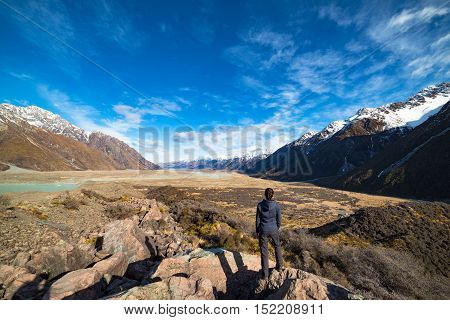 Vast and grandeur winter mountain landscape view from above. Tasman valley with snow covered mountains and woman looking at scenery. New Zealand