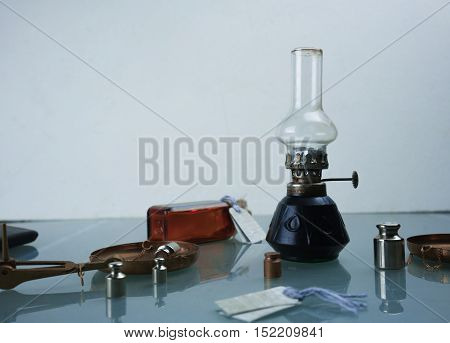 Hand scales with weights, a kerosene lamp. space for text