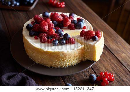 Homemade Christmas winter berry fruit cheesecake on wooden dark table. Creamy mascarpone dessert. ozy atmospheric photo.
