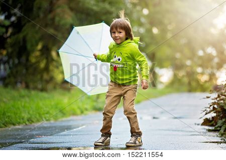 Adorable Little Boy With Umbrella In A Park On A Rainy Day, Playing And Jumping, Smiling