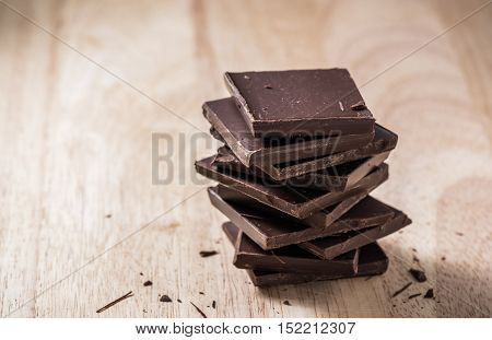 Dark Chocolate Bars Stack on Wooden Table. Place for Text.