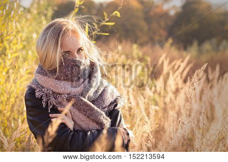 sad beautiful woman in scarf at autumn sunset, toned image