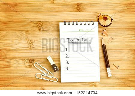 notepad with  pencil and smart phone on wooden table for to do check list concept , overhead shot or Top view