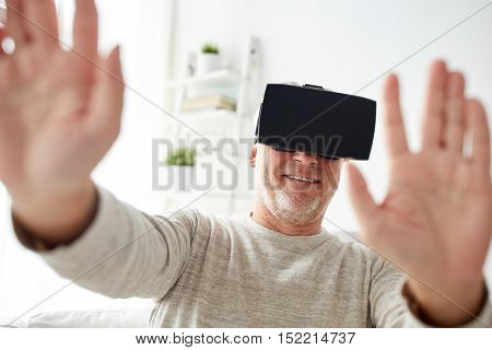 3d technology, augmented reality, gaming, entertainment and people concept - happy senior man with virtual headset or 3d glasses playing videogame at home