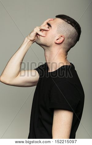Side-view of man with shaven temples in black t-shirt, who feeling shame and holding his right hand on face. Isolated