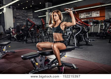 Muscular fitness woman doing exercises in the gym. Fitness - concept of healthy lifestyle.