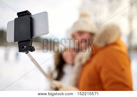 people, season, technology and winter concept - happy couple taking picture with smartphone selfie stick outdoors
