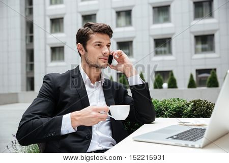 Handsome young businessman talking on mobile phone and drinking coffee in outdoor cafe