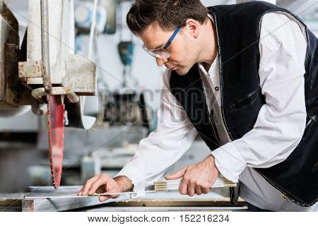 Handyman in stone carving factory at diamond saw