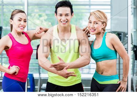 Muscular young man amongst two sportive women striking a pose and presenting his muscles