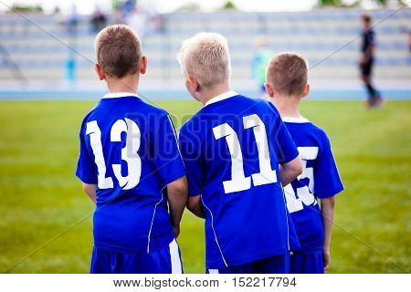 Children football soccer match. Team waiting on a bench. Ready to play soccer game