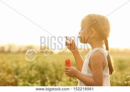 Little girl blowing bubbles in field