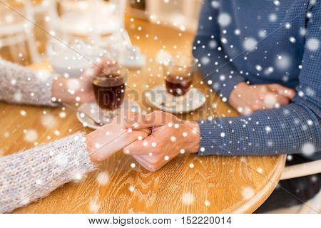 people, love, romance and dating concept - close up of happy couple drinking tea and holding hands at cafe or restaurant