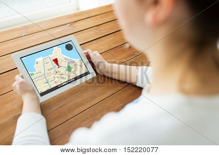 technology, people, navigation and location concept - close up of woman with gps navigator map on tablet pc computer screen on wooden table