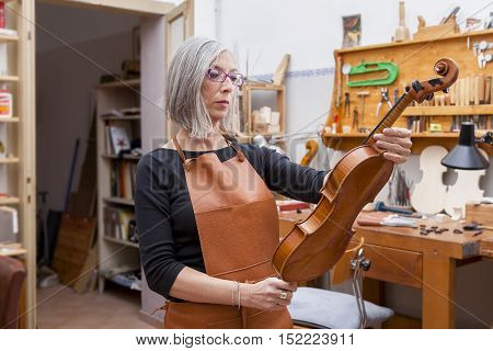 portrait of female mature violin maker while testing the violins in his laboratory