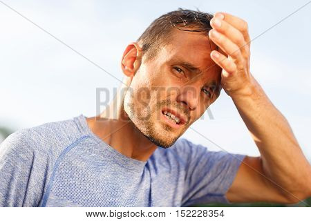 Portrait sporty man closeup wipes forehead with his palm after workout on nature
