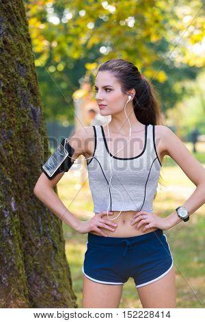Female Runner Wearing Earphones And Armband