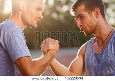 Two handsome strong athlete tense men handshake outdoors. Image with lens flare effect