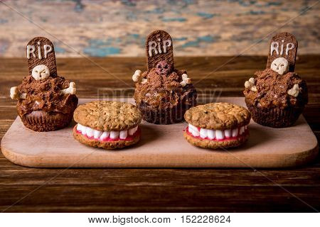 Dentures for Halloween made of cookies and marshmallow and Halloween cupcakes with tombstone cake topper on an old wooden table. Small cupcakes with gravestone with the inscription RIP. Holiday cookies for Halloween