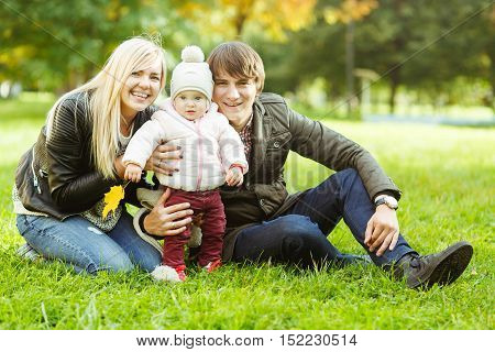 Cheerful parents with little daughter sitting on green grass in autumn park