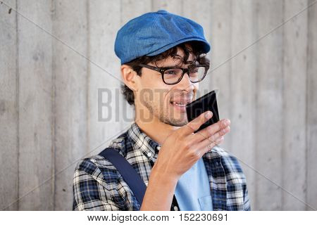leisure, technology, communication and people concept - smiling hipster man using voice command recorder or calling on smartphone at street wall