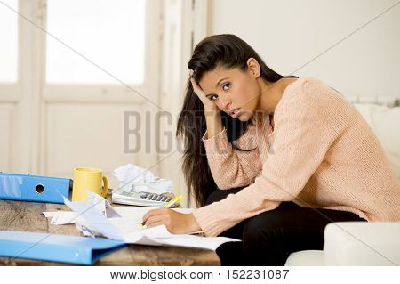 sad attractive latin woman at home living room couch calculating monthly expenses worried in stress with bank papers and documents in paying taxes mortage debt and cost of living concept