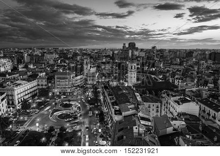 Aerial view of Valencia Spain at sunset. Illuminated Plaza de la Reina with many cafes and restaurants and very popular among tourists. Black and white