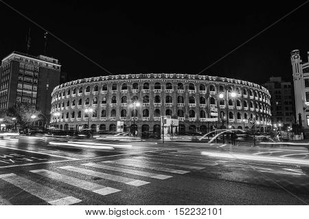 Night view of a Bullring Arena in Valencia Spain. Car traffic lighting trail motion blurred people. Dark sky. Black and white