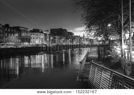 Embankment of Liffey River in Dublin Ireland. Night view with buildings and city lights at the background. Black and white