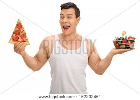 Tempted guy holding a pizza slice and a small shopping basket full of fruits and vegetables isolated on white background