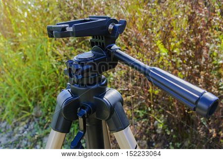Tripod for photo equipment in the grass near the lake