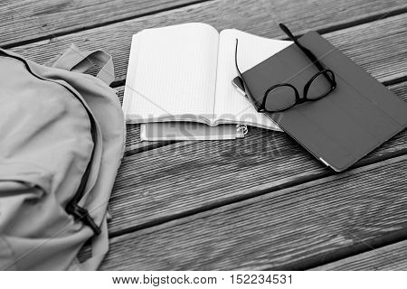 Subjects student -glasses, notebooks, Tablet, on wooden floor, black - white photo