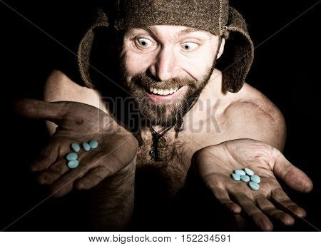Dark portrait of scary evil sinister bearded man with smirk, holds in palm of a bunch of pills. strange Russian man with a naked torso and a woolen hat.