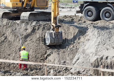 Worker, excavator digger and truck on a building site. Earthwork at construction site.