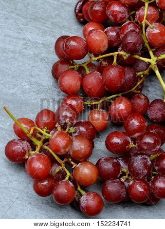 Red Seedless Grapes on a Grey Background: Closeup view from above.