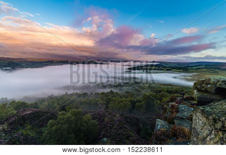 Colorful Surise Clouds over Valley Covered in Mist with Photography Camera on the Edge of Rocks