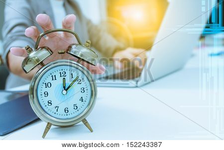 Business people write something about meeting subject on laptop computer and hand holding the clock ,business content and business background.
