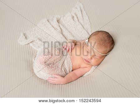 lovely smiling sleeping infant wrapped in gray warm diaper