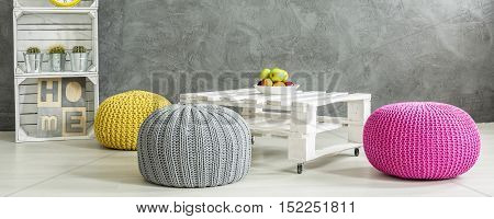 Grey Room With A Table Surrounded By Colorful Poufs
