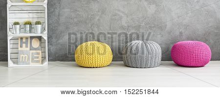 Colorful Poufs And A Shelf Against A Grey Wall