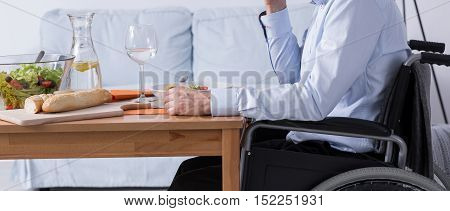 Close shot of a man on a wheel chair sitting at the table