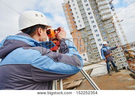 Two surveyors worker with theodolite